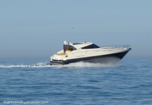 Speed boat with sunbather on the back near Golfo Aranci